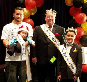 Pictured (l to r) are Mr. Popcorn Kernel Karson Freeman (held by his father, Brandon Freeman), 2017 Mr. Popcorn Don Bennett, and Mr. Popcorn Junior Brody Cahill.